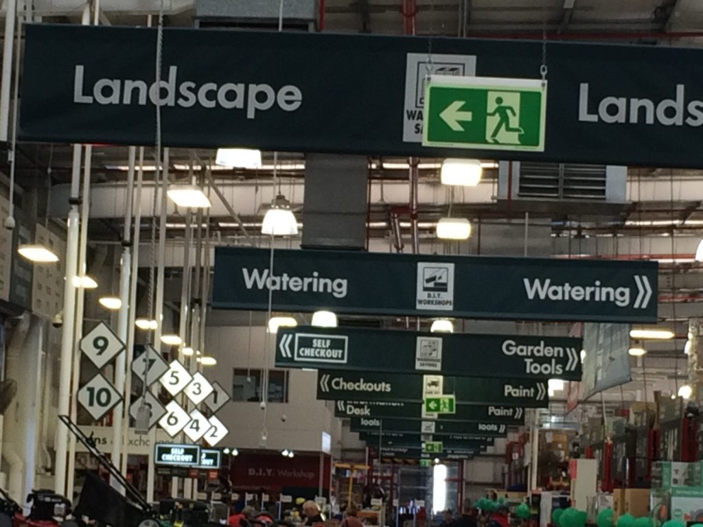 Photoluminescent exit signs visible through Bunnings near checkouts